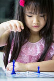 Little asian child playing chesse Stock Photo