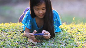 Little Asian child playing game on smart phone in the park stock video