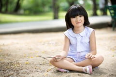 Little Asian child playing sand in the park Stock Image