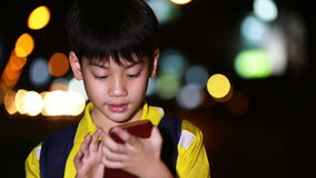 Little asian child playing with smart phone on night lights background stock video