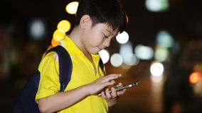 Little asian child playing with smart phone on night lights background stock video footage