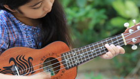 Little Asian child playing ukulele. In the park stock footage
