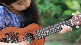Little Asian child playing ukulele stock footage