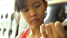 Little Asian child playing ukulele on sofa. Soft focus stock video footage
