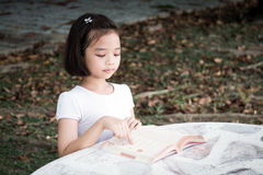 Little Asian child reading a book Royalty Free Stock Images