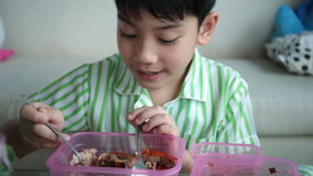 Little asian child sitting at table eating meal at home . stock video footage