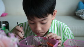 Little asian child sitting at table eating meal at home . stock video