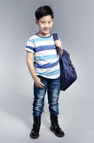 Little Asian child standing with a kit bag slung over his should Stock Images