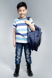 Little Asian child standing with a kit bag slung over his should Stock Photography