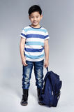 Little Asian child standing with a kit bag slung Royalty Free Stock Image