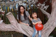 Happy smile child with mother mom and daughter play balloon outdoor family parental activity joyful childhood summer. A little Asian Chinese girl, have fun and royalty free stock photos