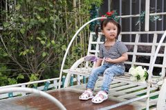 Happy cute naughty lovely adorable little girl play lolipop and sit on a carriage have fun outdoor in summer park. A little Asian Chinese girl, have fun and play royalty free stock photography