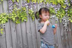Aisa cute naughty lovely adorable child girl play with balloon have fun outdoor in summer park happy smile happiness childhood. A little Asian Chinese girl, have Stock Photos