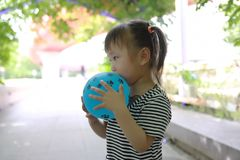 Aisa cute naughty lovely adorable child girl play with balloon have fun outdoor in summer park happy smile happiness childhood. A little Asian Chinese girl, have Royalty Free Stock Image