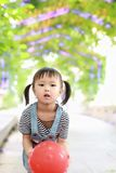 Aisa cute naughty lovely adorable child girl play with balloon have fun outdoor in summer park happy smile happiness childhood. A little Asian Chinese girl, have Stock Image