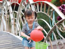Aisa cute naughty lovely child girl play with balloon have fun outdoor in summer park happy smile happiness funny childhood. A little Asian Chinese girl, have Stock Photography