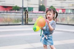 Aisa cute naughty lovely child girl play with balloon have fun outdoor in summer park happy smile happiness funny childhood. A little Asian Chinese girl, have Royalty Free Stock Images