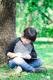 Little asian cute  boy writing book in the park Royalty Free Stock Photos