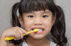 Little asian cute girl brush teeth .
