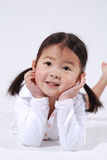 Little asian girl. Smiling little Asian girl, her mouth open and hands on her cheeks in surprise.  Laying on her stomach and leaning on her elbows, in a location Stock Images