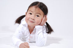 Little asian girl. Smiling little Asian girl, hands on her cheeks in surprise.  Laying on her stomach and leaning on her elbows, in a location setting.  Isolated Royalty Free Stock Images