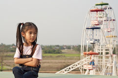 Little Asian girl in amusement park. Stock Photo