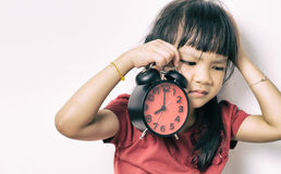 Little asian girl is angry at the alarm clock for waking her up. Royalty Free Stock Photos