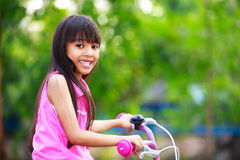 Little asian girl in a bicycle Royalty Free Stock Photo