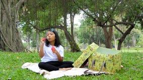 Little Asian girl blowing air bubbles. Little Asian girl blowing air bubbles under a tree in public park stock video