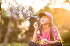 Little asian girl blowing soap bubbles. Outdoor at sunset Royalty Free Stock Photo
