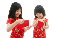 Little asian girl and boy holding red packet monetary gift Royalty Free Stock Images