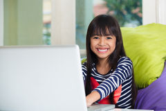 Little asian girl with computer Royalty Free Stock Photo