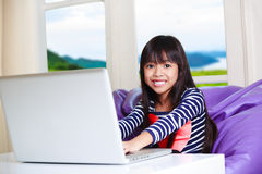 Little asian girl with computer Royalty Free Stock Images
