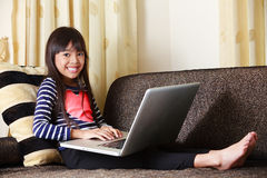 Little asian girl  with computer at home Royalty Free Stock Photo