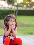 Little asian girl covering her mouth with her hands. Stock Photos
