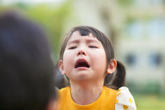Little asian girl crying and look at  her parents Stock Photo