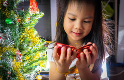 Little Asian Girl is Decorating Christmas Tree Royalty Free Stock Photography