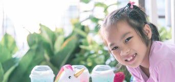 Little asian girl drinking Unicorn milk stock image