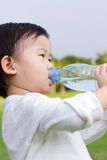Little asian girl  drinking water from plastic bottle Royalty Free Stock Photos