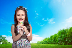 Little Asian Girl Eat Lollipop. Over park background Royalty Free Stock Images