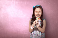Little Asian Girl Eat Lollipop. Over pink wall background Royalty Free Stock Photos