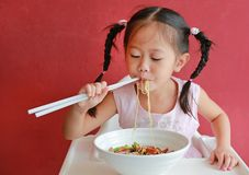 Free Little Asian Girl Eating Egg Noodle With Roasted Duck And Pork On High Chair Against Red Wall Background Stock Photos - 156691963