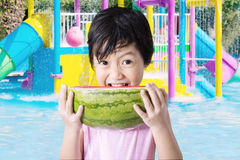 Little Asian girl eating fresh watermelon. Portrait of little Asian girl eating a slice of fresh watermelon on the swimming pool Stock Image