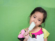 Little Asian girl eating ice cream. In summer Royalty Free Stock Photography