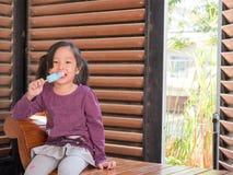 Little Asian girl eating ice cream. Wood shade stripes background Royalty Free Stock Image