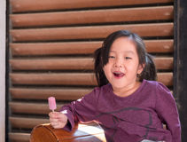 Little Asian girl eating ice cream. Wood shade stripes background Royalty Free Stock Images