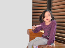 Little Asian girl eating ice cream. Wood shade stripes background Royalty Free Stock Photos