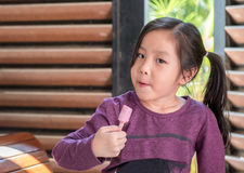 Little Asian girl eating ice cream. Wood shade stripes background Royalty Free Stock Photo