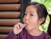 Little Asian girl eating ice cream. Wood shade stripes background Royalty Free Stock Photography
