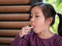 Little Asian girl eating ice cream. Wood shade stripes background Stock Photography